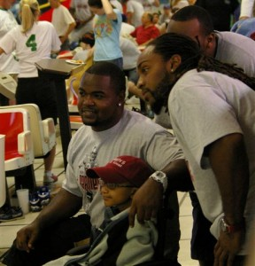 Bucs fullback Chris Pressley (left) and Kareem Huggins share a moment with a young fan at Earnest Graham's charity bowling event in Fort Myers. Graham's foundation, Earnest Giving, is helping kids with cancer. (Photo by Kyra Hallett, JoeBucsFan.com)