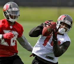 Buccaneers WR Robert Herron grabs a pass in front of CB Rashaan Melvin.