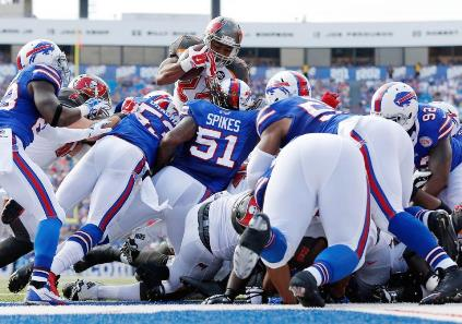 The Bucs offensive line gets just enough of a push to allow Doug Martin to sky over the Buffalo defense for a first half touchdown Saturday. Photo courtesy of Buccaneers.com.