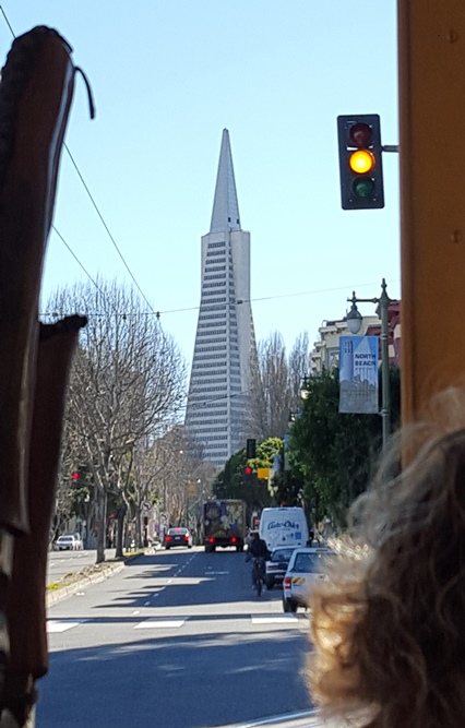 Looking down a street while cruising through the city on a cable car.