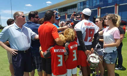 Former Bucs kicker Martin Gramatica (red shirt) with his two sons as well as current Bucs kicker Roberto Aguayo (19) surrounded by a gaggle of reporters after Bucs OTA practice today.