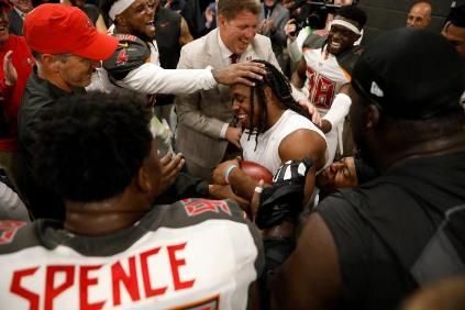 Jacquizz Rodgers is mobbed after being awarded the game ball last night.